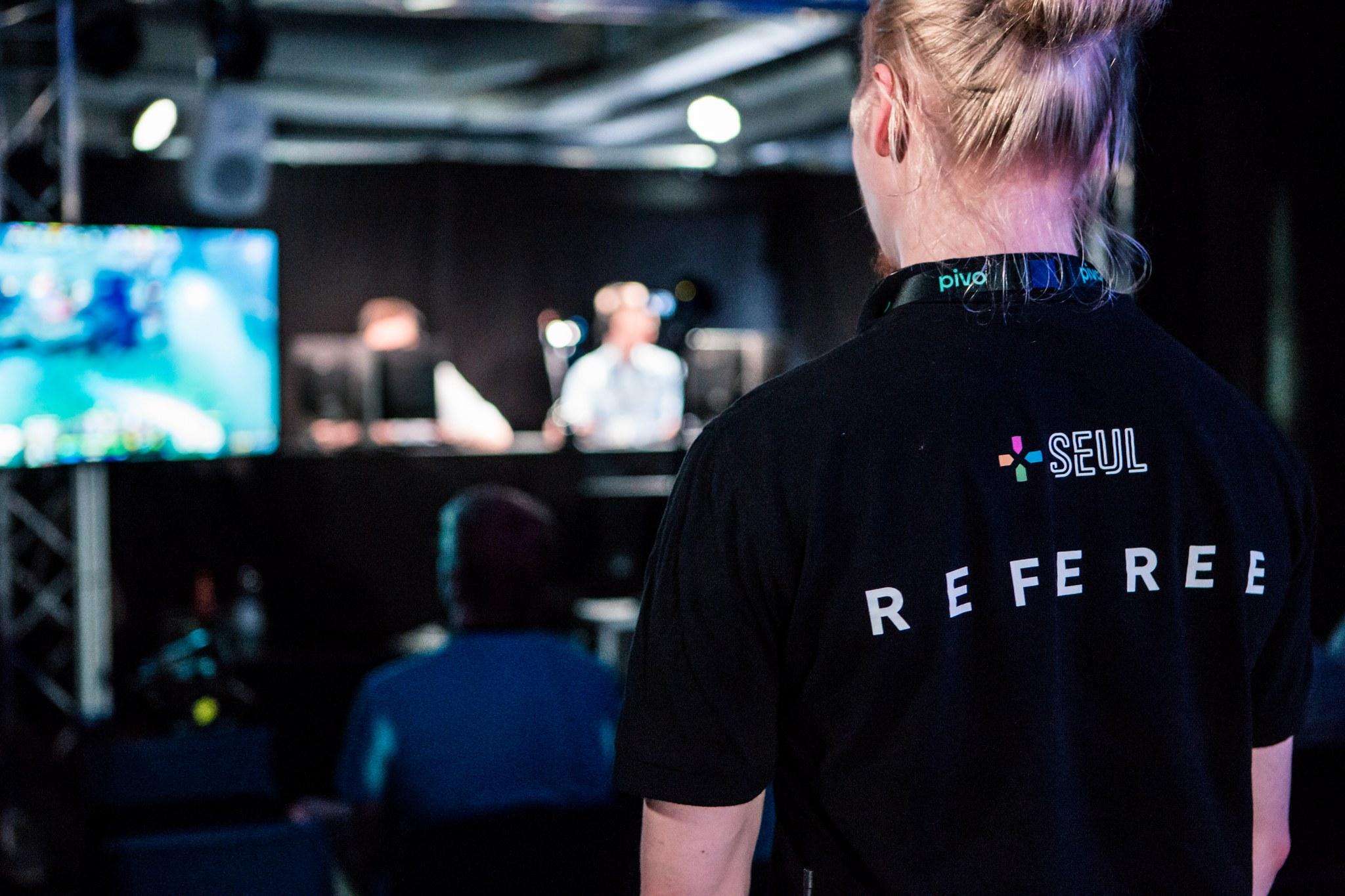 """Mies selkä päin kameraa, paidan selässä on teksti """"referee""""."""
